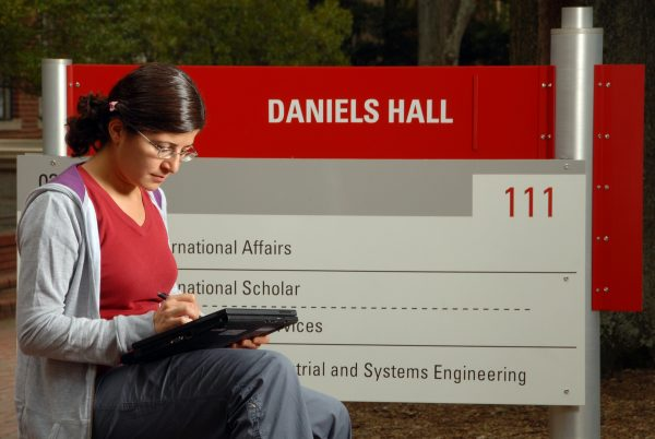 Before heading inside for class, an ISE student works on her computer in front of Daniels Hall.
